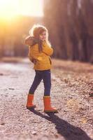 Little girl in orange jacket and rubber boots photo