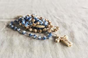 Brown rosary with blue details with image of Jesus on the cross photo