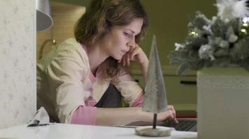 une jeune femme travaille sur un ordinateur à la maison video