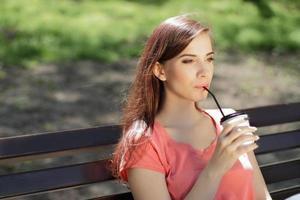 mujer tomando café en un banco del parque foto
