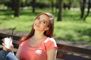 Woman holding a drink on a park bench photo