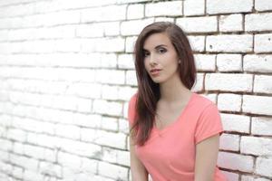 mujer en una pared de ladrillo blanco foto