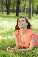 mujer mirando hacia arriba mientras está acostado en la hierba foto