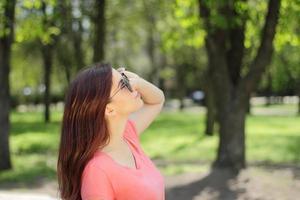 mujer mirando hacia arriba y con gafas de sol foto