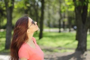 Woman looking up in a park photo