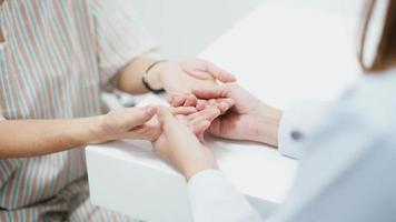Gros plan d'un médecin tenant la main d'un patient âgé video