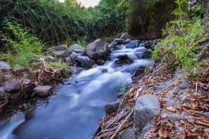 Corriente de agua pura que fluye sobre terrenos montañosos rocosos en el bosque de Kakopetria en Troodos Chipre foto