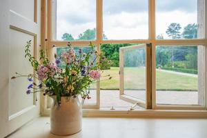 Flowers and window view into gardens from a traditional English stately home photo
