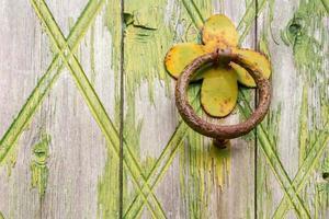 Door handle-knocker on old wooden door photo