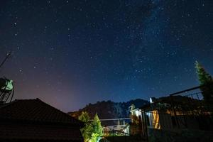 Stars and Milky Way over the forest and a house at the Troodos mountains photo