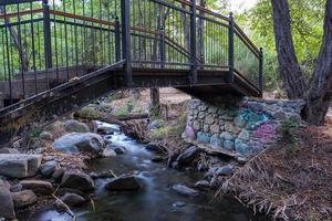 Bridge over smooth flowing water stream at the Vateri Footpah in Kakopetria in Cyprus photo