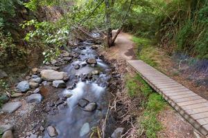 Corriente de agua pura que fluye sobre terrenos montañosos rocosos a lo largo del sendero vateri en el bosque de Kakopetria en Troodos, Chipre foto