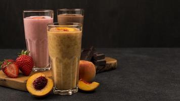 Selection of three milkshake glasses with chocolate and fruit photo