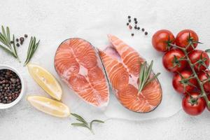 Slices of raw red salmon and tomatoes photo