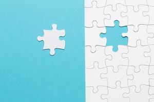Single white jigsaw puzzle pieces on blue background photo