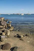 La paz baja california sur malecón por el mar de Cortés con rocas en la playa y agua de mar tranquila con el mogote al fondo foto