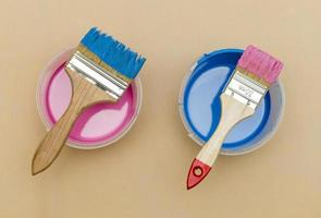 Top view pink and blue brushes on paint buckets photo