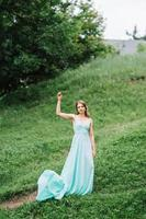 Happy girl in a turquoise long dress in a green park photo