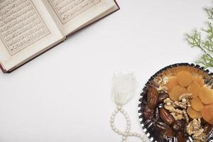 Snacks and quran on white table photo