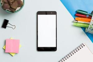 Smartphone surrounded by office supplies photo