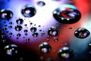 A shiny colorful surface with tiny droplets photo