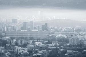 Heavily polluted city in blue monochrome photo