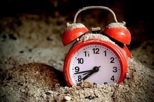 Red alarm clock in ash photo
