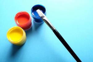 Pinturas al óleo y un pincel sobre fondo azul. foto