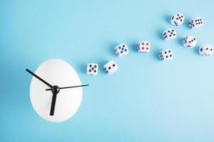 An egg clock with dice on blue background photo