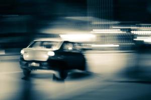 Blurry monochrome image of a moving car photo