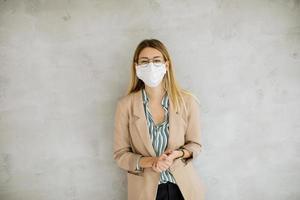 profesional de negocios contra un fondo gris con una máscara foto