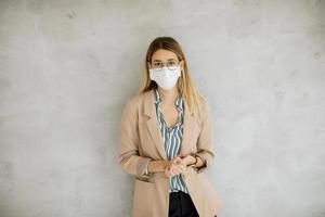mujer recostada contra la pared y con una máscara foto