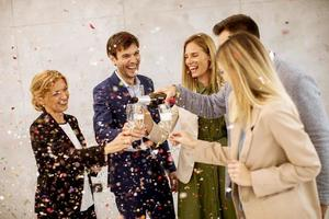 Group toasting with confetti falling photo