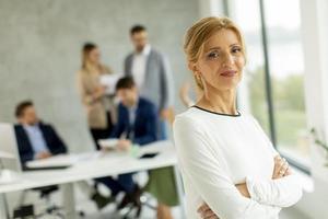 primer plano, de, un, mujer de negocios, con, compañeros de trabajo, en, fondo foto