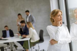 mujer mirando por la ventana con una reunión de negocios detrás de ella foto