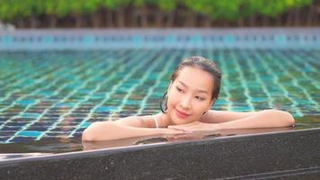 Young Asian Woman Relaxing Around an Outdoor Swimming Pool video