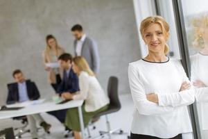 Mujer apoyada contra una ventana con compañeros de trabajo en el fondo foto