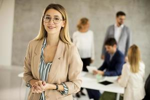 mujer con gafas frente a una reunión foto