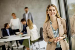 Woman in glasses with meeting in the background photo