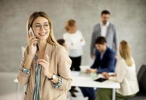 Woman on phone with meeting in the background photo