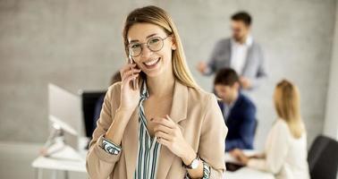 mujer hablando por teléfono con una reunión en el fondo foto