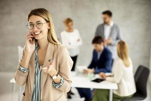 Woman talking on phone with meeting in the background photo