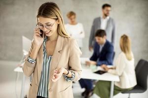 mujer hablando por teléfono con compañeros de trabajo en el fondo foto