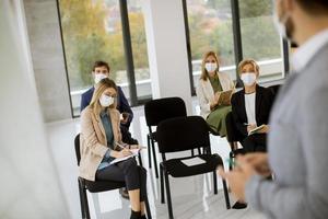 profesionales en reunión con máscaras en foto