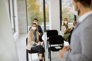 orador y multitud con máscaras en reunión foto