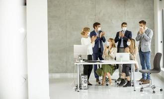 Group of masked professionals clapping photo