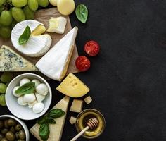 Various types of cheese, grapes, honey, and snacks photo