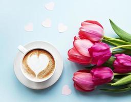 taza de café con arte latte y tulipanes foto