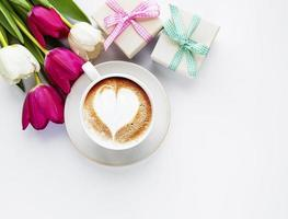 Coffee cup with latte art and tulips photo