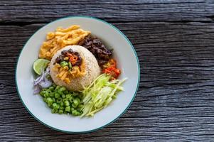 Thai shrimp paste fried rice with sweet pork on wooden table, top view photo